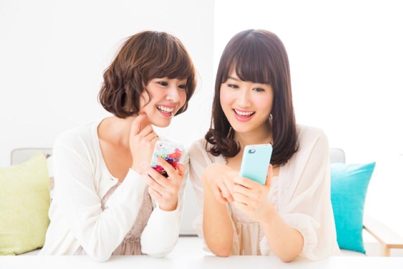 スマホを見る若い女性二人