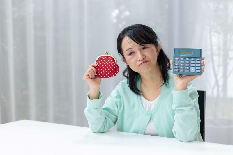 財布と電卓を持っている悩む女性