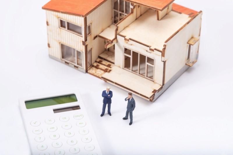 家の模型と電卓と人の模型
