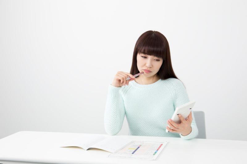 本と電卓と悩む女性