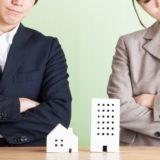 白い家の模型を見ている男性と女性