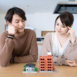 2つの家の模型を見て考えるカップル