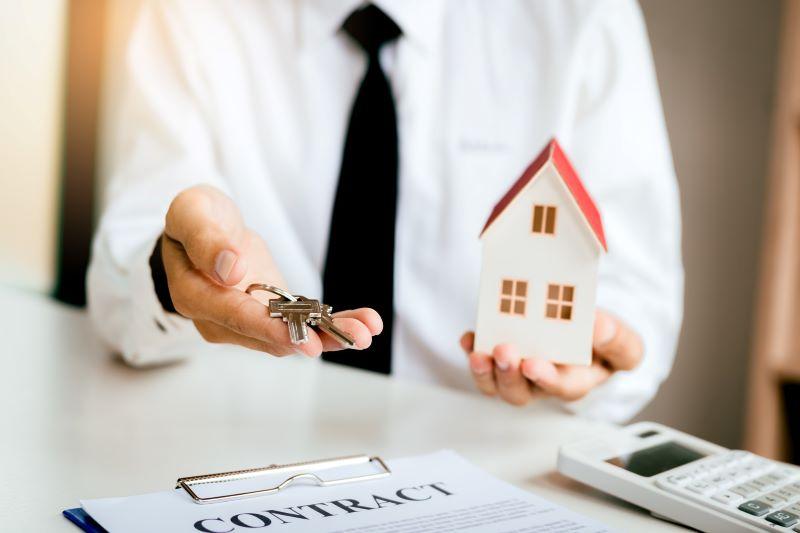 鍵と家の模型を渡しているスーツの男子