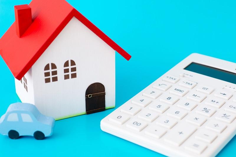 赤い屋根の家模型と白い電卓