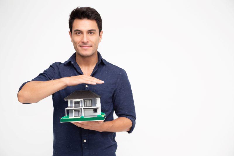 家の模型を持っている外国人