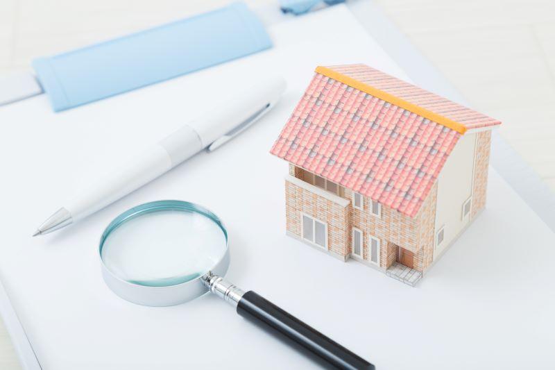 拡大鏡とボールペンと家の模型