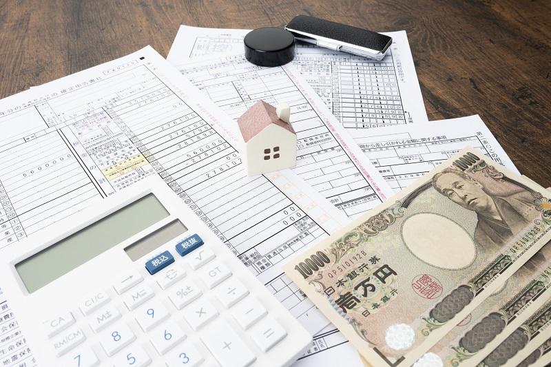 白い電卓と四枚の書類と4枚の一万円札