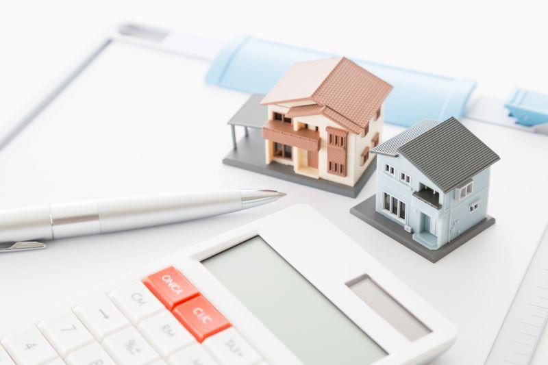 電卓と2つの家の模型とボールペン
