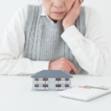 悩む老人と家の模型