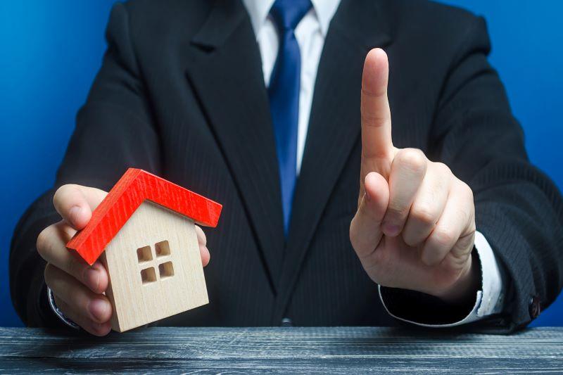 家の模型と一の指をしているスーツの男子
