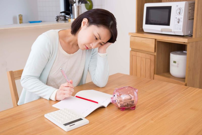 本と電卓と貯金箱と悩む主婦