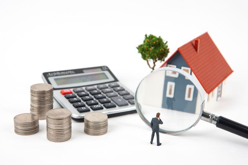 小銭と電卓と家の模型