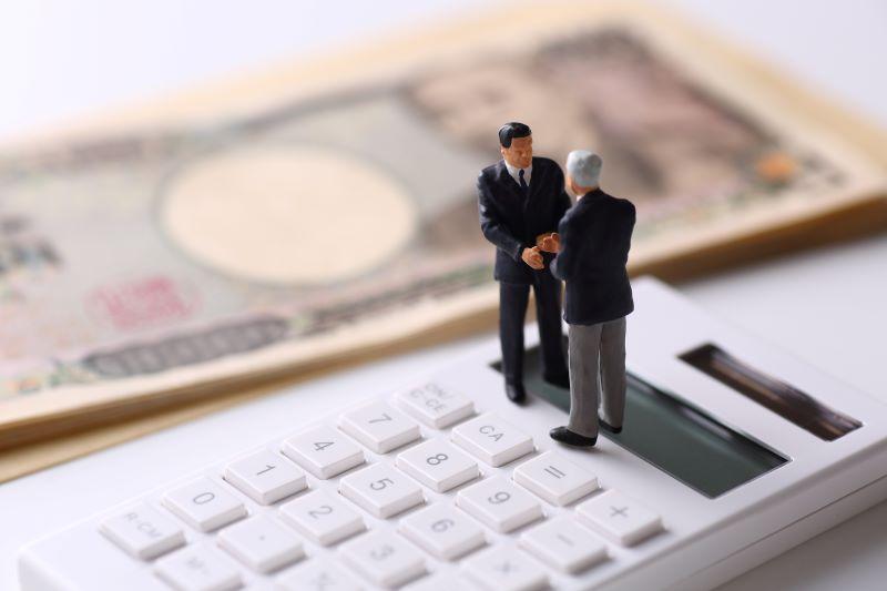 お金と電卓と握手している二人