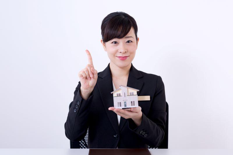 家の模型と1の指をしている女性