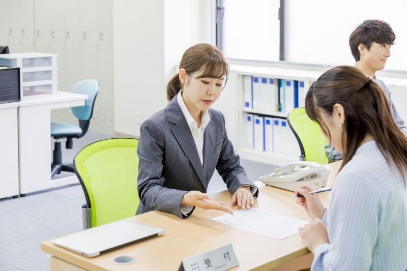 受付で書類作成している女性