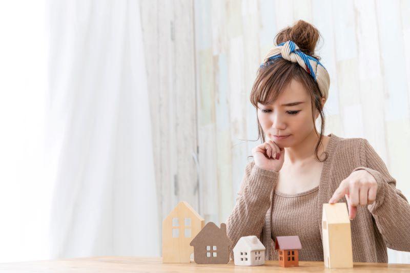 家の模型と悩む女性