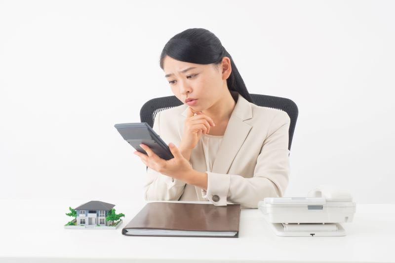 電卓と資料と悩む女性