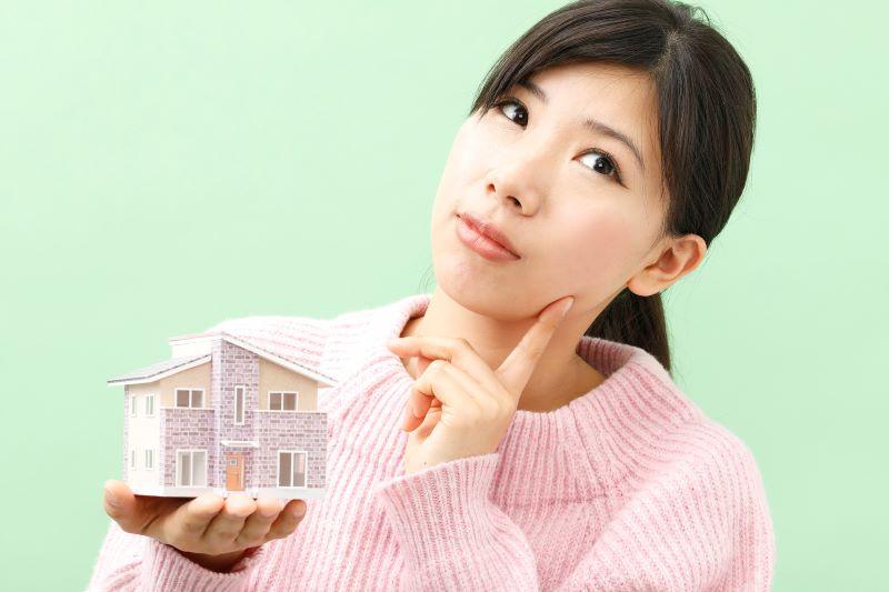 家の模型を持っている悩む女性